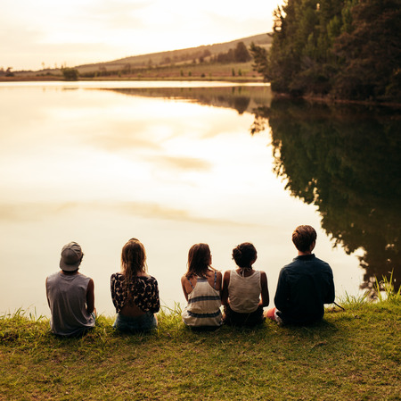 5: Rear view image of group of young friends sitting in a row by a lake and looking at a beautiful landscape view. Group of friends sitting by a lake and relaxing.