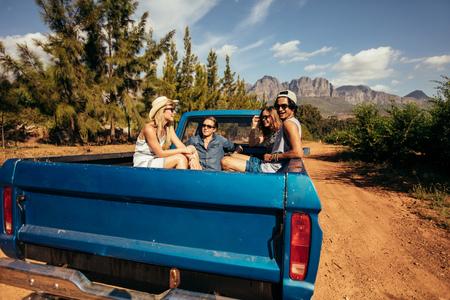데리 러 자동차의 뒤쪽에 앉아 친구의 그룹. 젊은 남녀가 자연 여행을 떠납니다.