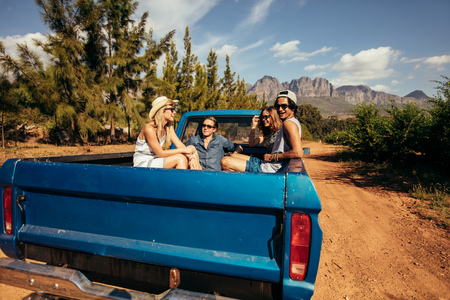 Group of friends sitting at the back of a pick up car. Young men and women going on a road trip in nature.