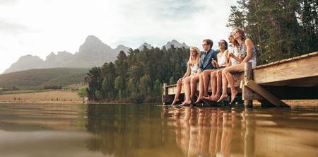 Retrato de jóvenes amigos felices que se sientan en el embarcadero en el lago para beber cervezas. Los hombres jóvenes y una mujer que disfruta de un día en el lago.