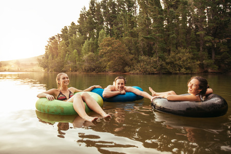 Portrait of happy young friends in inflatable rings floating on lake. Young people relaxing in water on a summer day. Enjoying their holidays at the lake.