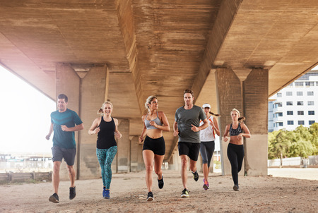Group of athletes running on a road under bridge in the city. Young men and women jogging, training together in morning.