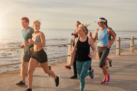 motion: Porträtt av ungdomar som kör vid havet i morgon, friska unga män och kvinnor att göra löpträning.