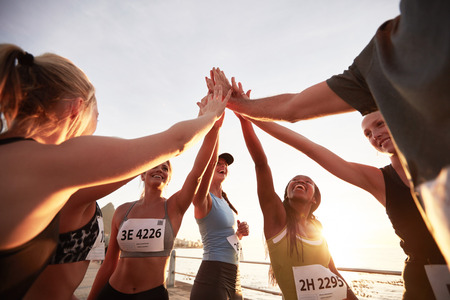 personas corriendo: Los corredores de alto chocando entre s� despu�s de una buena sesi�n de entrenamiento. Grupo de atletas dan unos a otros de alta cinco despu�s de la carrera.