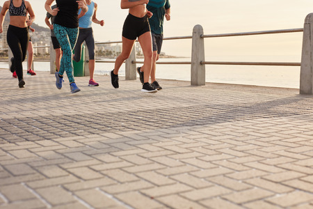 cropped shot: Low section cropped shot of people running on street by the sea. Fitness group training on seaside promenade.