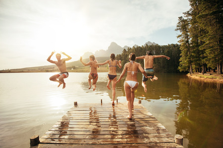 Achter portret van de jonge vrienden springen in een meer. Jongeren rennen en springen van een steiger in een meer op een zonnige dag.