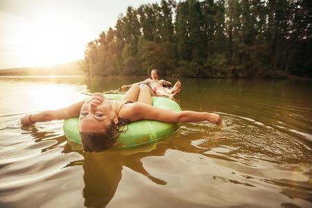 schwimmring: mit einem Mann Porträt in einem innertube im Hintergrund in einem See schwimmenden jungen Mädchen lächelnd. Junge Paare in der See auf aufblasbaren Ringen. Lizenzfreie Bilder