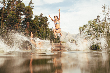 diving: Portrait of young women jumping into a wilderness lake from the jetty. Young girl jumping from a pier at the lake
