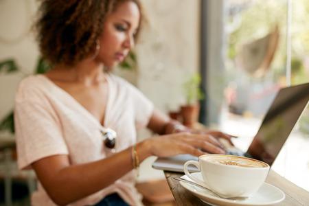 백그라운드에서 노트북을 사용하는 젊은 여자와 테이블에 신선한 카푸치노 한잔. 카페에서 커피 잔의 초점입니다.