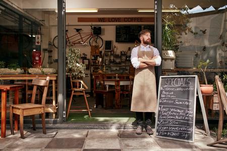 Ritratto di un giovane uomo in piedi davanti al suo negozio di caffè. Giovane con la barba che porta un grembiule in piedi con le braccia incrociate e guardando lontano.