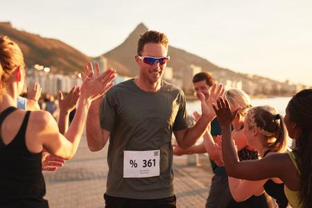 fila de personas: Grupo de adultos jóvenes animando y alta fiving una línea de meta de cruce atleta masculino. Deportista dando de alta cinco de su equipo después de terminar la carrera. Foto de archivo