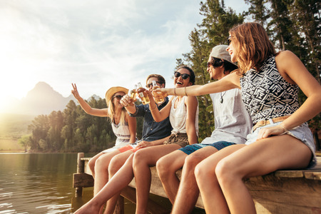 Portrait of young friends sitting on a pier and toasting beers. Happy young men and women having beers at the lake on a sunny day. Stockfoto