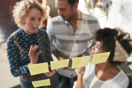 Drei Geschäftsleute, die ein Treffen im Amt. Sie stehen vor der Glaswand mit post-it-Zetteln und zu diskutieren. Standard-Bild