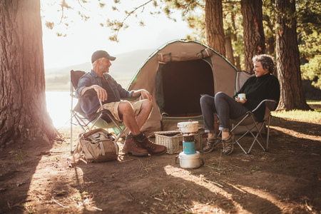 tent: Portrait of happy senior couple sitting in chairs by tent at campsite. Mature man and woman relaxing and talking near a lake on a sunny day. Stock Photo