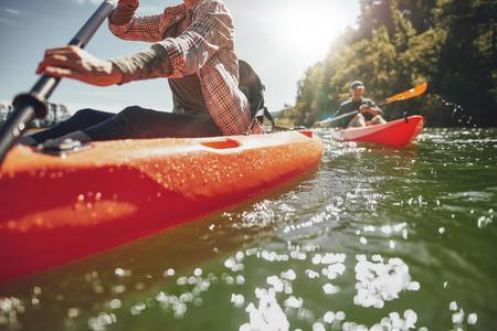 Imagem colhida da mulher de caiaque com um homem em segundo plano. Casal de canoagem em um lago em um dia de verão.