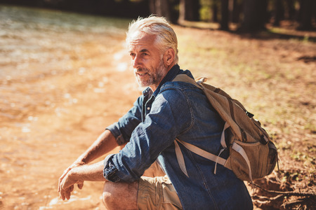 Portrait of senior male hiker sitting next to a lake and looking away. Mature man taking a break from his hike and looking at the view Stock Photo