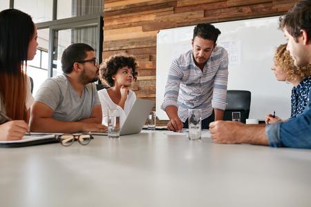 Mladí obchodní tým na setkání diskutovat pokrok společnosti. Kreativní profesionálové sedí kolem stolu v kanceláři.