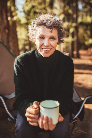 looking to camera: Portrait of senior woman sitting outside the tent with a cup of coffee. Caucasian female holding a coffee cup looking at camera and smiling at campsite.