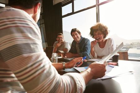 Schot van gemengd ras jonge mensen zitten aan een tafel bespreken van nieuwe en creatieve zakelijke ideeën. Glimlachende Afrikaanse vrouw zitten met collega's in een vergadering. Stockfoto
