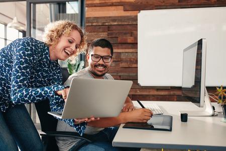 Schot van twee gelukkige jonge grafische ontwerpers werken in hun kantoor met een man zit aan zijn bureau en vrouwelijke collega blijkt iets op haar laptop.