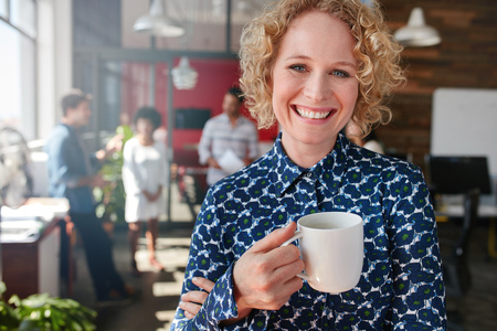 Portrait of cheerful female designer holding a cup of coffee. She is standing in office with colleagues discussing in background.