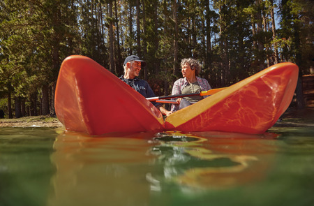 two woman: Active senior couple in two single kayaks side by side. Mature man and woman looking at each other and smiling while kayaking in a lake.