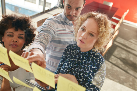 tormenta de ideas: Retrato de profesionales creativos que buscan a través de una pared de post-it nota y la lluvia de ideas. el hombre y la mujer joven de pie en la oficina detrás de la pared de vidrio con notas adhesivas. Foto de archivo