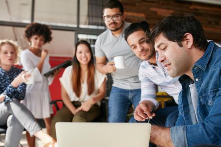 함께 젊은 비즈니스 사람들이 회의에서 새로운 창조적 인 프로젝트에 토론을 데의 그룹입니다. 시작 회의를 팀에 게 뭔가 보여주는 젊은 디자이너. 스톡 콘텐츠
