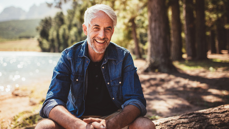 Portrait of happy mature man sitting near a lake looking at camera and smiling. Senior caucasian man sitting on a log by the lake on a summer day.