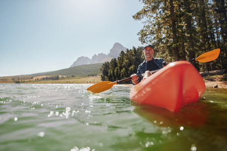 Rear view of a senior man canoeing in a lake on a sunny day. Senior man paddling kayak.