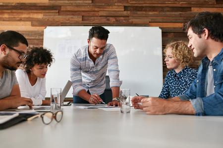 회의에서 시작 팀 작업 및 계획. 회의실 테이블에 새로운 창조적 인 아이디어를 논의하는 젊은 전문가의 팀.
