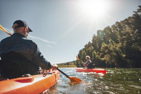 高級情侶在一個陽光燦爛的日子在湖中劃獨木舟的形象。皮划艇運動員在湖中戲水。 版權商用圖片