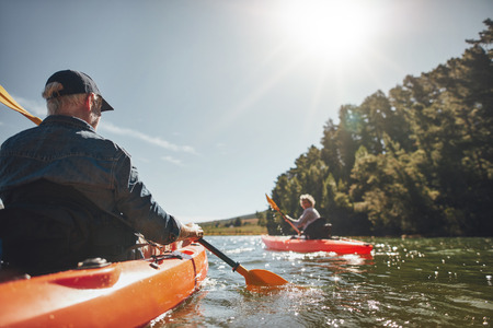female senior adults: Image of senior couple canoeing in the lake on a sunny day. Kayakers in the lake paddling.