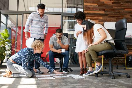 Творческие люди, глядя на план проекта выложен на полу. Смешанная раса деловых партнеров обсуждают новый план проекта в современном офисе.