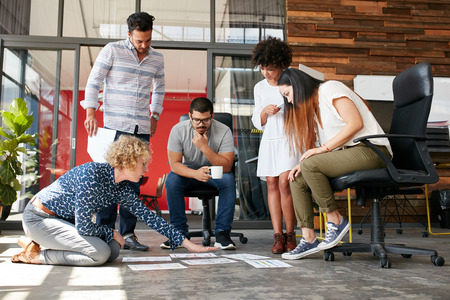 Creative people looking at project plan laid out on floor. Mixed race business associates discussing new project plan in modern office. Stockfoto
