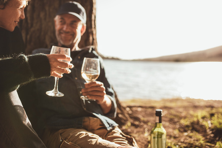Close up portrait of senior couple drinking wine while camping near a lake. Focus on hands holding glass of wine.