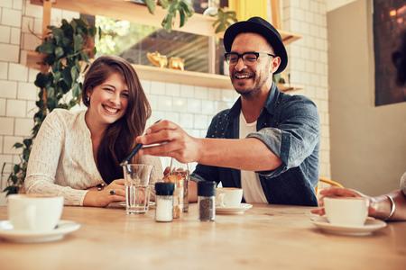 カフェに座っている友人に彼の携帯電話を示す幸せな若い男の肖像画。