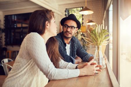 Portret van jonge man en vrouw zitten in een cafe en praten. Jong koppel ontspannen in een koffiewinkel. Stockfoto