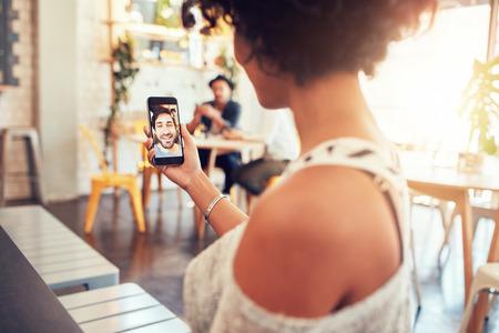 Man en vrouw praten met elkaar door middel van een video-oproep op een smartphone. Jonge vrouw met een videochat met een man op de mobiele telefoon. Vrouw zitten in een cafe. Stockfoto