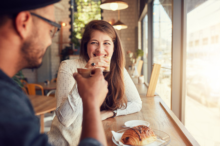 Portrait of a casual young couple having coffee together at the coffee shop. Young man and woman meeting at cafe.