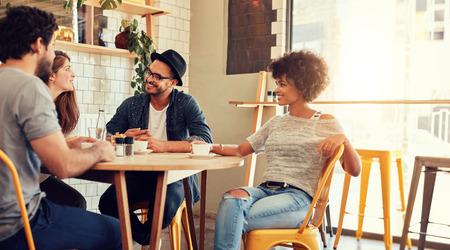 Portret młodej grupy przyjaciół, którzy spotkali się w kawiarni. Młodzi mężczyźni i kobiety siedzą przy stoliku kawiarni i rozmawiają.