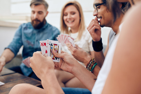 man holding card: Group of friends sitting together playing cards. Focus on playing cards in hands of a woman during a party.