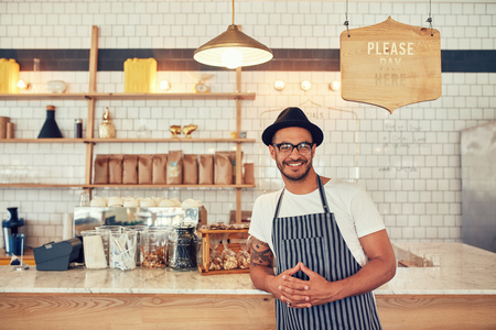 looking to camera: Portrait of happy young man wearing an apron and hat leaning to a cafe counter. Male barista standing at coffee shop looking at a camera and smiling.