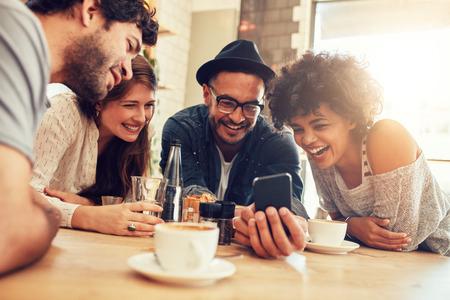 Портрет веселых молодых друзей, глядя на смартфон, сидя в кафе. Смешанная раса людей, сидя за столом в ресторане с помощью мобильного телефона.