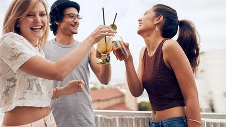 Portret van een jonge vrouw roosteren cocktail met haar vrienden tijdens een feestje. Drie jonge vrienden genieten in een partij. Jonge man en vrouw opknoping samen.