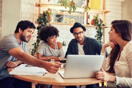 ノート パソコンでカフェでテーブルを囲んで座っている若者の肖像画。創造的なチームはコーヒー ショップで新しいビジネス プロジェクトについて議論します。