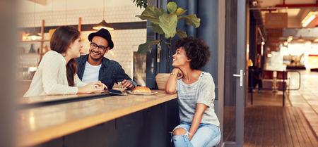Portret van drie jonge mensen zitten samen in een cafe. Groep jonge vrienden bijeen in een coffeeshop.