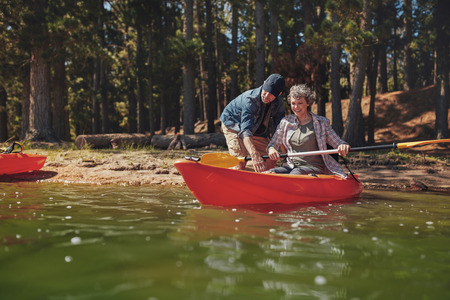 Portrait of mature woman learning to row in kayak. Man teaching kayaking to woman at the lake. Stock Photo
