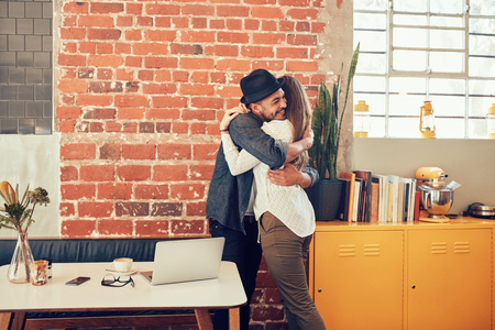 Portrait of young couple embracing each other at a coffee shop. Young man hugging his girlfriend at a cafe.