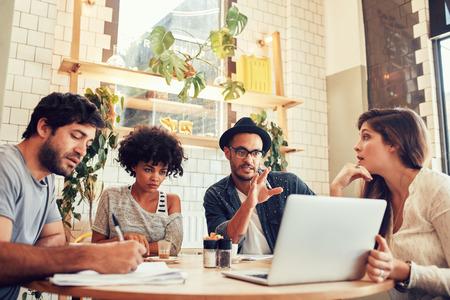 노트북과 커피 숍에 앉아 창조적 인 비즈니스 팀의 초상화. 카페에서 동료들과 함께 새로운 비즈니스 아이디어를 논의하는 젊은 남자.
